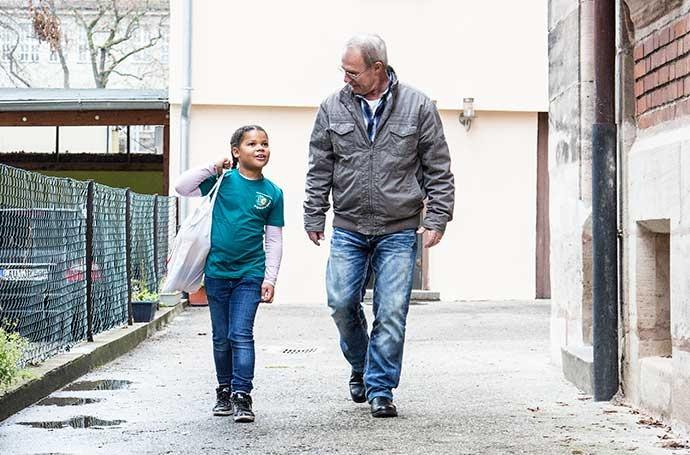 Eine junge Jugendrotkreuzlerin trägt die Einkaufstasche eines älteren Mannes.