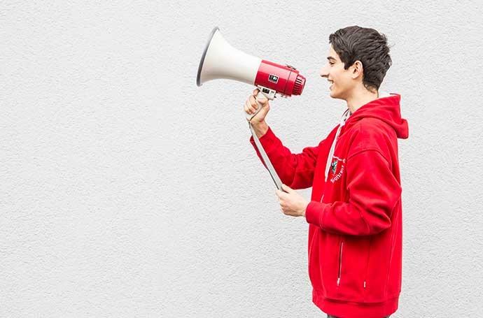 Ein Jugendrotkreuzler hält ein Megaphon in der Hand.